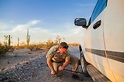 "03 MAY 2012 - VEKOL VALLEY, RURAL PINAL COUNTY, AZ:    Jon Young (CQ Jon), the BLM  Chief Ranger for Arizona, changes a flat tire on his vehicle on Bureau of Land Management land south of Interstate 8 and west of Casa Grande in rural Pinal County. The area has been a hotbed of illegal immigrant and drug smuggling for years. The BLM has undertaken a series of ""surges"" in the area, increasing their law enforcement patrols and partnering with Border Patrol and Pinal County Sheriff's Department officers to reduce criminal activity in the area.       PHOTO BY JACK KURTZ"