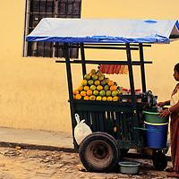 Central America, Guatemala, Antigua. A Guatemalan orange juice vendor attends her cart in Antigua, Guatemala.