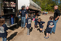 Jim Phelps and Jeff Pierson ask Elm Street School kindergarteners to count the tires on the oil truck during their field trip to Foley Oil on Wednesday morning.  (Karen Bobotas/for the Laconia Daily Sun)