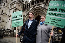 © Licensed to London News Pictures. 21/02/2017. London, UK. Heterosexual couple REBECCA STEINFELD and CHARLES KEIDAN hold banners while posing for a photograph, as they arrive at Royal Courts of Justice in London, where a Court of Appeal ruling is due on whether a heterosexual couple can have a civil partnership. Photo credit: Ben Cawthra/LNP