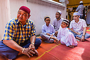 "08 AUGUST 2013 - BANGKOK, THAILAND: Men and boys wait outside of Haroon Mosque for Eid services to start. Eid al-Fitr is the ""festival of breaking of the fast,"" it's also called the Lesser Eid. It's an important religious holiday celebrated by Muslims worldwide that marks the end of Ramadan, the Islamic holy month of fasting. The religious Eid is a single day and Muslims are not permitted to fast that day. The holiday celebrates the conclusion of the 29 or 30 days of dawn-to-sunset fasting during the entire month of Ramadan. This is a day when Muslims around the world show a common goal of unity. The date for the start of any lunar Hijri month varies based on the observation of new moon by local religious authorities, so the exact day of celebration varies by locality.      PHOTO BY JACK KURTZ"