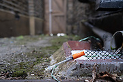 A discarded insulin syringe lies on the ground near a drain in a residential alleyway, on 25th November 2020, in London,England. Accorind to the NHS (National Health Service, syringes should be disposed of in a sharps bin - a specially designed box with a lid that can be obtained on prescription (FP10 prescription form) from a GP or pharmacist. When full, the box may be collected for disposal by a local council.