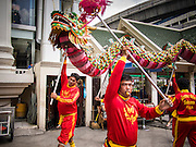 17 AUGUST 2013 - BANGKOK, THAILAND:    A Dragon dance troupe performs at Erawan Shrine in Bangkok. The Chinese Dragon Dance began during the Han Dynasty which lasted from 206 BC to 24 AD. In those ancient days it was performed by the people of China specifically to please their ancestors and to insure sufficient rain for a plentiful crop. In this way they hoped to protect against hunger and sickness. Over time the Dragon Dance became a central feature in Chinese celebrations with different colors symbolizing different characteristics or desired features; red for excitement, green for a good harvest, yellow for a solemn empire and gold or silver for prosperity. The Dragon Dance is a well-choreographed event whose difficulty is dependent upon the performers' skill. The length of the dragon indicates just how much luck it will bring in the coming year, but a longer dragon requires more performers with great skill as an error by one can ruin the entire performance. The dragon is typically between 82 and 229 feet long. The head along can weigh as much as 31 pounds. Both strength and skill are both required in performing the Chinese Dragon Dance.        PHOTO BY JACK KURTZ