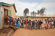 The children of Kibera School, Nairobi, line up to get their lunchtime meal.  There are 6 teachers with approximately 60 children in each class.  Undugu Society of Kenya (USK), a local NGO run various programmes to help the school and pupils including a lunchtime feeding program.