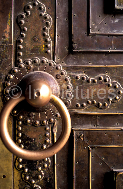 Detail of the entrance door pull of the Muslim Id Kah mosque, Kashgar city. It began life in its present form in 1798, before this time it had been a place of worship during the Ming dynasty (1368-1644), built on a smaller mosque dating back to the 15th century. It is the largest mosque in western China with the purest Uighur ( a Muslim minority of Turkic origin) architecture, its colours reflecting the arid environment it inhabits. Inside it contains a large octogonal shaped pavilion and internal courtyard which can allow up to 7000 worshipers in at any one time. It is the symbol of Uighur cultural and religious presence  for the whole of the central Chinese and neighbouring Asian countries, such as Kyrgyzstan, Tajikistan, Uzbekistan, Turkestan, Afghanistan, and Pakistan.