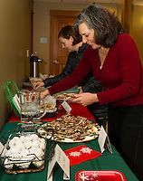 Alison Howe and Virginia Field choose from salted caramel pretzel chocolate chip cookies, butterballs, sugar cookies, angel wings, ginger snaps, peanut butter and chocolate toffee brittle and brown eyed susan cookies shared during the Cookie Swap at the Gilford Library on Tuesday evening.  (Karen Bobotas/for the Laconia Daily Sun)