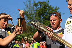 © Licensed to London News Pictures. 23/05/2012. CHIPPENHAM, UNITED KINGDOM. The Olympic torch is lit for Marathon running fireman Rob Warwick at the start of the Chippenham stage of the Olympic Torch relay in Wiltshire on Day 4 of the round Britain procession. Photo credit: Mark Chappell/LNP