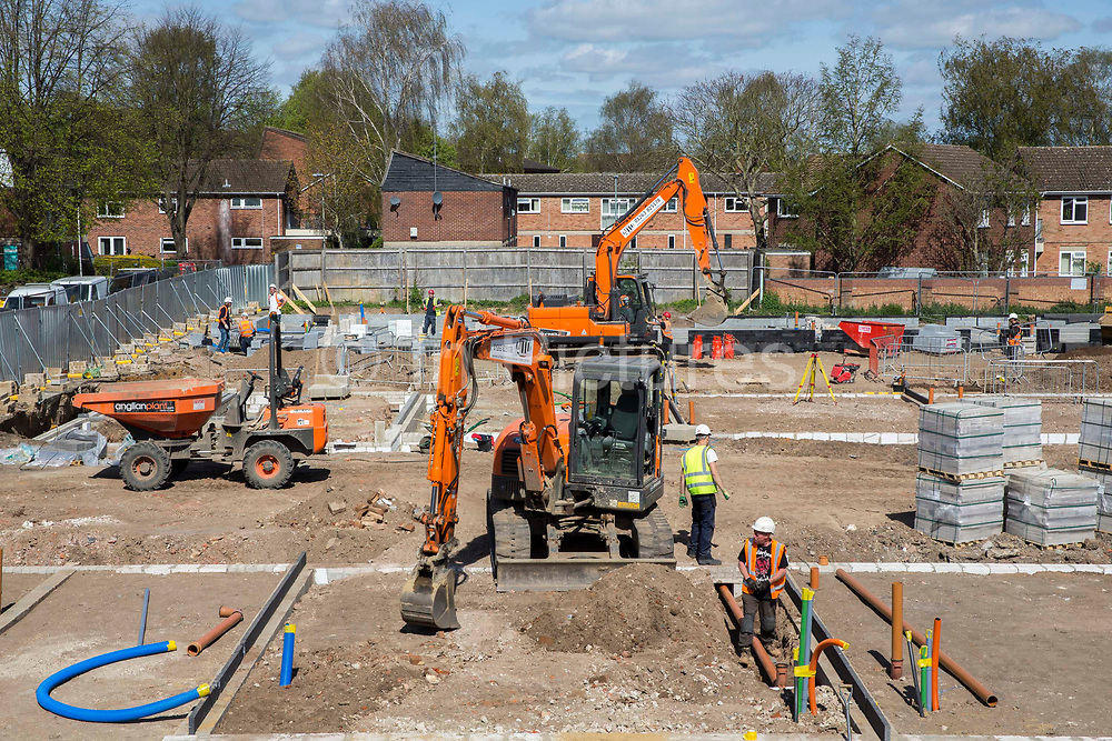 Builders use orange JCBs to lay drainage pipes in the ground around the foundations of a new build housing construction site in Norwich, Norfolk.  United Kingdom