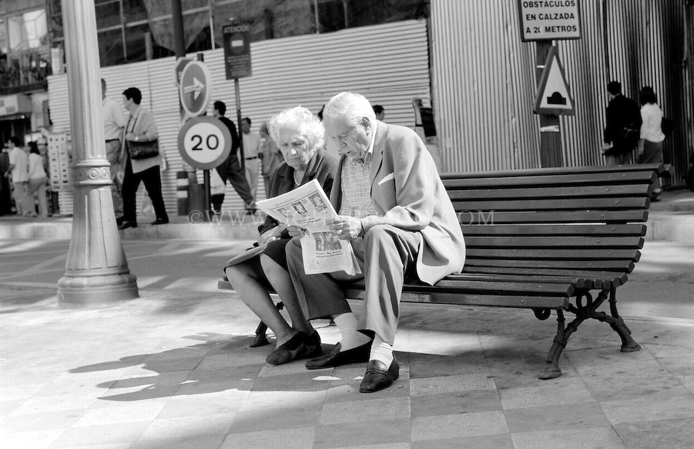 Black and white photo of an elderly couple reading the newspaper on a bench in Granada, Spain.