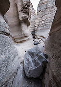 """Slot Canyon Trail. See fantastic hoodoos and a great slot canyon in Kasha-Katuwe Tent Rocks National Monument, in New Mexico, USA. Hike the easy Cave Loop Trail plus Slot Canyon Trail side trip (3 miles round trip), 40 miles southwest of Santa Fe, on the Pajarito Plateau. Distinctive cone-shaped caprocks protect soft pumice and tuff beneath. Geologically, the Tent Rocks are made of Peralta Tuff, formed from volcanic ash, pumice, and pyroclastic debris deposited over 1000 feet thick from the Jemez Volcanic Field, 7 million years ago. Kasha-Katuwe means """"white cliffs"""" in the Pueblo language Keresan."""