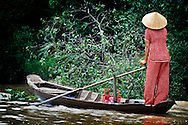 Young woman rowing a boat in the Mekong Delta.