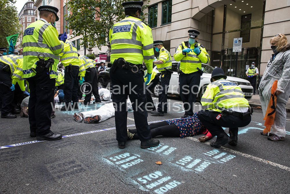 Metropolitan Police officers issue warnings to climate activists from Extinction Rebellion, some of whom wearing hazmat suits, who had occupied the street outside the Department of Transport in protest against roadbuilding on 3 September 2020 in London, United Kingdom. Extinction Rebellion activists are attending a series of September Rebellion protests around the UK to call on politicians to back the Climate and Ecological Emergency Bill (CEE Bill) which requires, among other measures, a serious plan to deal with the UK's share of emissions and to halt critical rises in global temperatures and for ordinary people to be involved in future environmental planning by means of a Citizens' Assembly.