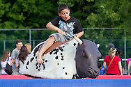 Newburgh, New York - A boy rides a mechanical bull during the Relay for Life of Newburgh at Cronomer Hill Park on June 8, 2013. The Relay for Life is the American Cancer Society's signature fundraising event. Participants celebrate the lives of people who have battled cancer, remember loved ones lost, and fight back against the disease by raising money.