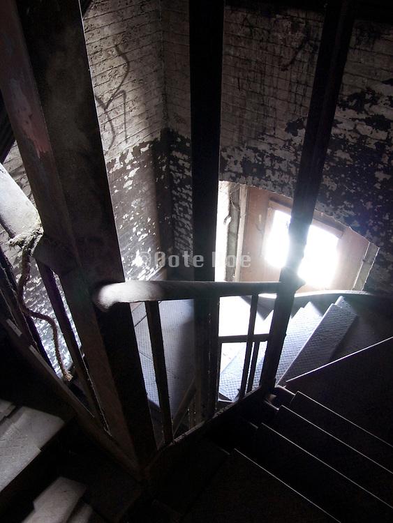 dark fire escape stairway in industrial building looking down