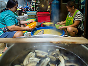 """07 FEBRUARY 2018 - BANGKOK, THAILAND:  Women in Bangkok's """"Chinatown""""  sort boiled mung beans used in desserts consumed during Lunar New Year celebrations. The Lunar New Year, also called Tet or Chinese New Year, is 16 February this year. The coming year will be the Year of the Dog. Thailand has a large Chinese community and Lunar New Year is widely celebrated in Thailand, especially in Bangkok and large cities with significant Chinese communities.     PHOTO BY JACK KURTZ"""