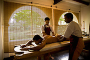 A patient has warm medicated oil poured over his whole body to massage him for as part of the overall Ayurveda experience at Kalari Kovalikom, Kerala, India.