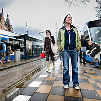 """Nederland, Amsterdam , 19 oktober 2011..Journaliste Jorie Horsthuis tussen de trams op het Centraal Station..Jorie Horsthuis is journaliste voor o.a. De Groene Amsterdammer en heeft zojuist een boek geschreven met als titel """"Op de Tram""""..Foto:Jean-Pierre Jans"""