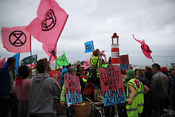 "© Licensed to London News Pictures . 22/09/2019. Brighton, UK. Environmental campaigners from Extinction Rebellion highlight the climate emergency and deploy a large red and white lighthouse lightship named "" Greta "" , on Brighton Promenade , during the second day of the 2019 Labour Party Conference from the Brighton Centre . Photo credit: Joel Goodman/LNP"