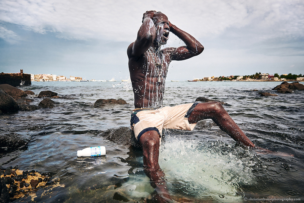 On  August 11, 2015, Kherou Ngor pours cow milk over his head and body. He performs this ritual in the water at the shore of Ngor, Dakar, in order to obtain the spiritual support of a ghost who lives in the stones at the shore. Cow milk and magic potions are omnipresent in the wrestling arenas of Senegal, where vodoo and gris-gris rituals are a undisposable part of the show for the audience.