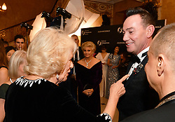 The Duchess of Cornwall admires the lapel badge of Craig Revel-Horwood at the Julien Macdonald Fashion Show Reception at Lancaster House in London, which is supporting the National Osteoporosis Society charity.