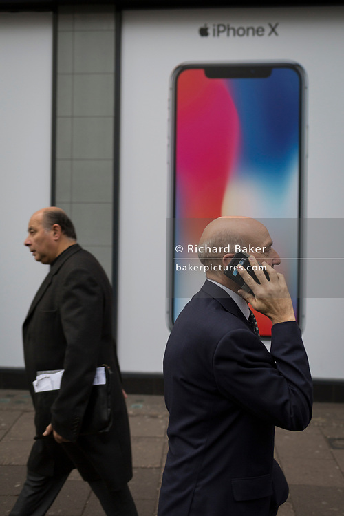 Men walk past an ad for the new Apple iPhone X outside a branch of Carphone Warehouse, on 22nd November 2017, in London England.