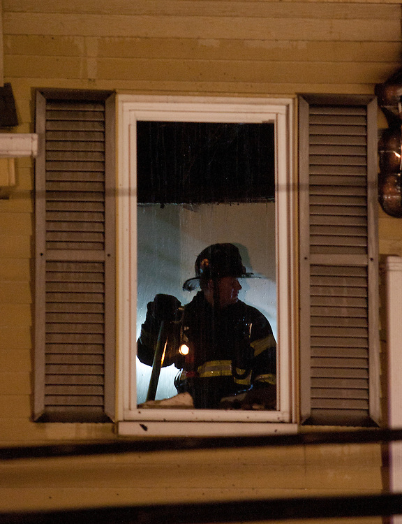 Quincy, MA 10/09/2011.Quincy Fire Department firefighters work at the scene of a 2 alarm house fire at 44 Penn St. on Sunday night..Alex Jones / www.alexjonesphoto.com