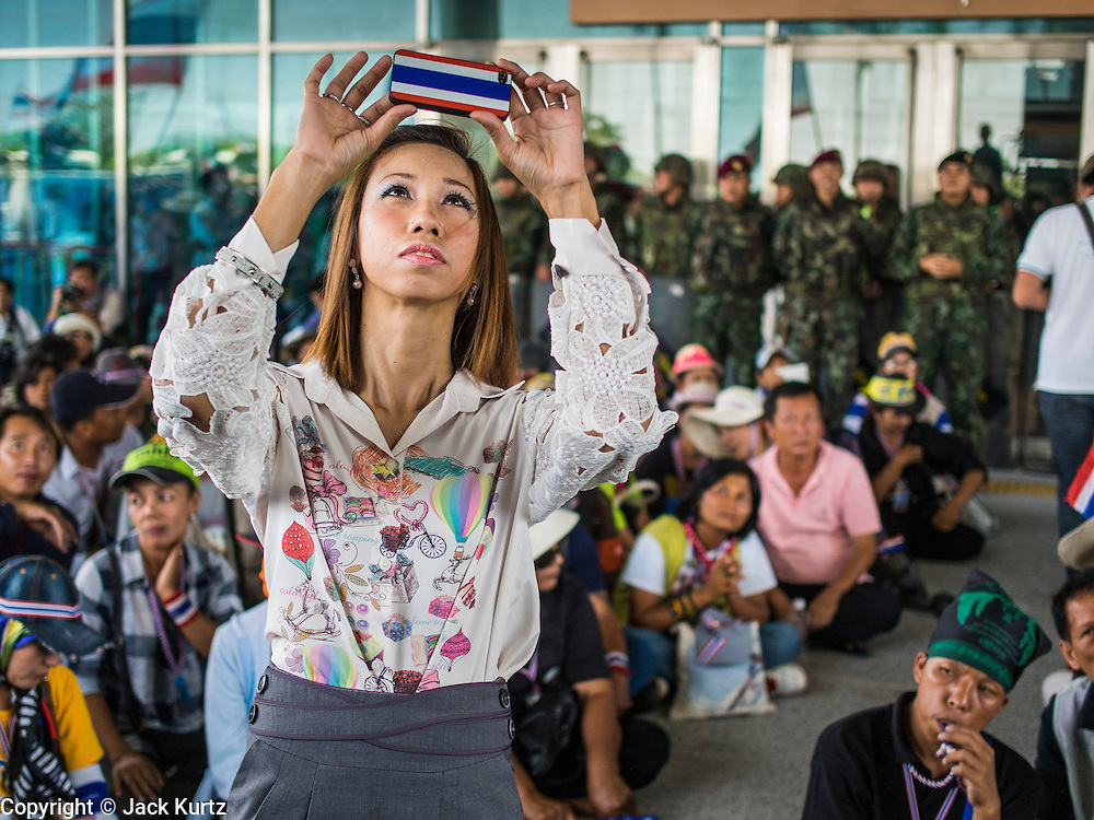 "08 APRIL 2014 - BANGKOK, THAILAND: A Ministry of Justice employee uses her iPhone, which has a case modeled on the Thai flag, to photograph anti-government protestors in front of the Ministry. Several hundred anti-government protestors led by Suthep Thaugsuban went to the Ministry of Justice in Bangkok Tuesday. Suthep and the protestors met with representatives of the Ministry of Justice and expressed their belief that Thai politics need to be reformed and that corruption needed to be ""seriously tackled."" The protestors returned to their main protest site in Lumpini Park in central Bangkok after the meeting.    PHOTO BY JACK KURTZ"