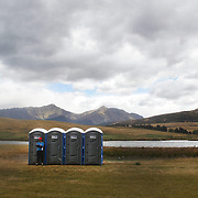 A race spectator watches from Portable toilets in a nearby field during the Active Q T Ultimate Tri Series Jack's Point Triathlon, Jack's Point,  Queenstown, Otago, New Zealand. 14th January 2012. Photo Tim Clayton