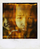 Old Polaroid of young Laotian boy looking at the camera with a furrowed brow and emotional expression, while his mother smiles in the background, Laos, Southeast Asia.