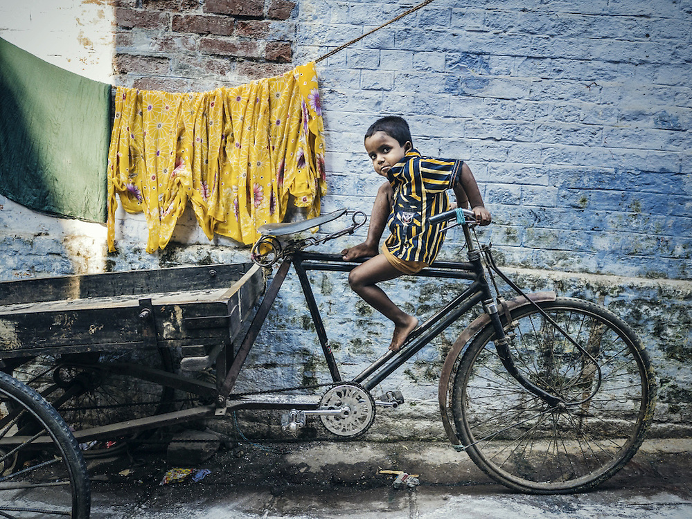 Varanasi, India - October 06, 2015. Small boy on a bicycle in one of the streets of the old quarter of Varanasi India. This is the holiest city of hinduism and also one of the oldest inhabited cities in the world with a maze of small alleys and streets along the Ganges river