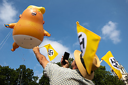 """© Licensed to London News Pictures . 13/07/2018. London, UK. Anti Trump flags made up of four """"T"""" shapes are waved by an onlooker as an inflatable Donald Trump blimp depicting the US president as a nappy wearing baby is launched from Parliament Square over Westminster. Demonstrators protest against a visit by US President Donald Trump to the UK . Photo credit: Joel Goodman/LNP"""