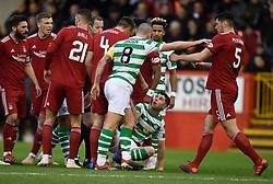 Celtic's Scott Brown pushes Aberdeen's Scott McKenna (right) as Ryan Christie sits on the ground during the Scottish Premiership match at Pittodrie Stadium, Aberdeen.