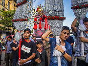 03 NOVEMBER 2014 - YANGON, MYANMAR: Shia Muslims in Yangon carry a coffin representing Hussein bin Ali's coffin through the streets of Yangon during the celebration of Ashura. Shia Muslims in Yangon started the celebration of Ashura Monday. Ashura commemorates the death of Hussein ibn Ali, the grandson of the Prophet Muhammed, in the 7th century. Hussein ibn Ali is considered by Shia Muslims to be the third Imam and the rightful successor of Muhammed. He was killed at the Battle of Karbala in 610 CE on the 10th day of Muharram, the first month of the Islamic calendar. According to Myanmar government statistics, only about 4% of Myanmar is Muslim. Many Muslims have fled Myanmar in recent years because of violence directed against Burmese Muslims by Buddhist nationalists.    PHOTO BY JACK KURTZ