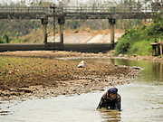 01 APRIL 2016 - WANG NUEA, LAMPANG, THAILAND:  A man fishes in the bottom of the Mae Wang (Wang River) in Wang Nuea. The river should be waist deep at this time of year but is barely ankle deep. The man said he had never seen the river so low. It is so low that water cannot flow past the irrigation gate in the background. The Mae Wang flows into the Chao Phraya River and on to Bangkok and provides domestic and irrigation water for much of northern Thailand. The rainy season is not expected to start for at least two more months.     PHOTO BY JACK KURTZ