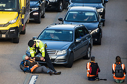 Ockham, UK. 21st September, 2021. A Surrey Police officer prepares to drag an Insulate Britain climate activist from the anticlockwise carriageway of the M25 between Junctions 9 and 10 where they had been protesting as part of a campaign intended to push the UK government to make significant legislative change to start lowering emissions. Both carriageways were briefly blocked before being cleared by Surrey Police. The activists are demanding that the government immediately promises both to fully fund and ensure the insulation of all social housing in Britain by 2025 and to produce within four months a legally binding national plan to fully fund and ensure the full low-energy and low-carbon whole-house retrofit, with no externalised costs, of all homes in Britain by 2030.