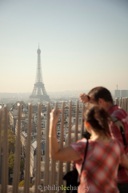 Tourists on the top of the Arc de Triomphe look to the iconic Eiffel Tower in Paris, France