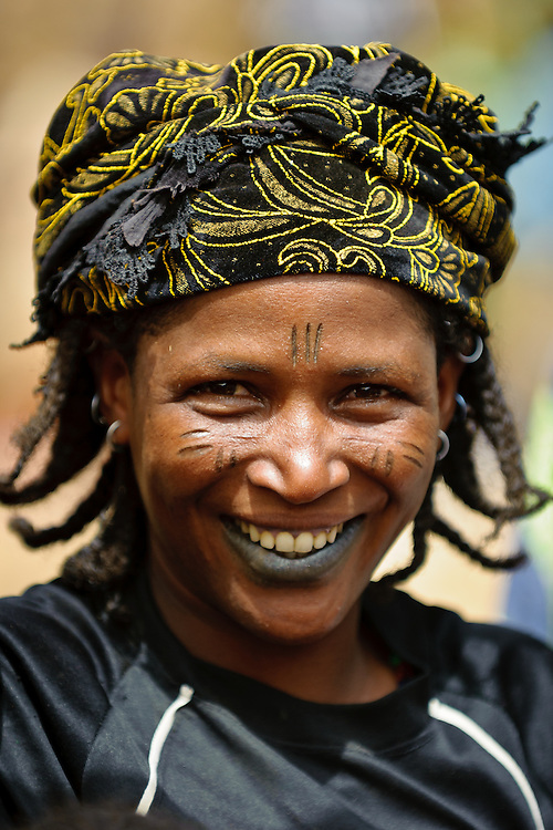 Portrait of a Fulani woman in a local market in northern Burkina Faso. The Fulani or Peul are nomadic herdsmen of the Sahel region of West Africa. The darker lower lip from indigo staining, facial tattoos and silver jewellery are traditional markings of Fulani women.