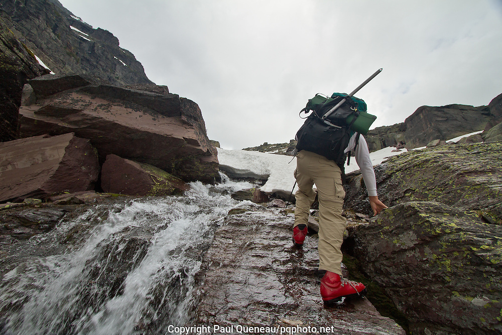 A backpacker climbs wet rock in Glacier National Park during an early summer backpacking trip.