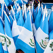 A cluster of small Guatemalan blue and white national flags for sale at a market for Guatemalan Independence Day.