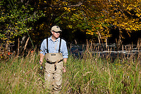 Male angler walking along the bank while fly fishing for trout on the upper Connecticut River in northern New Hampshire.