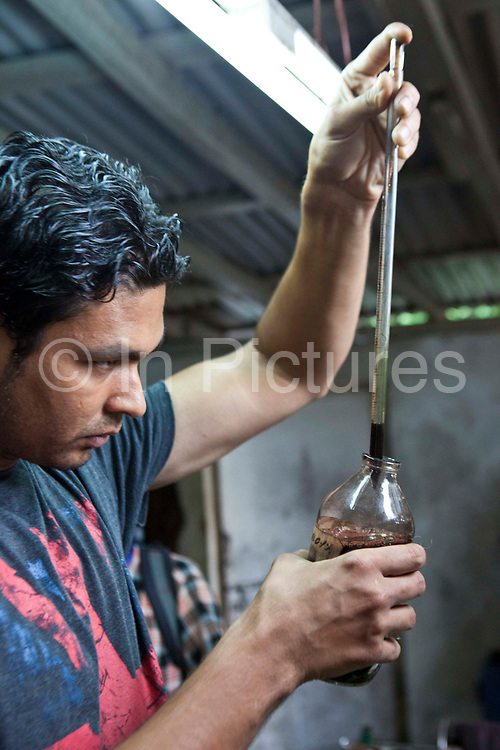 A Nepalese male factory worker mixes dyes to create dye solutions to color wool in R.C. Rug Factory in Narayanthan area of Kathmandu, Nepal.  He uses a pipette and glass bottle to draw up the dye solution. The R.C Rug Factory export to Europe, U.S and Canada; and rely on the GoodWeave certificate of approval to boast excellent quality and fair conditions for its workers. This is because the carpet factory industry in Nepal is notorious for providing poor working conditions and forcing young children into labour.