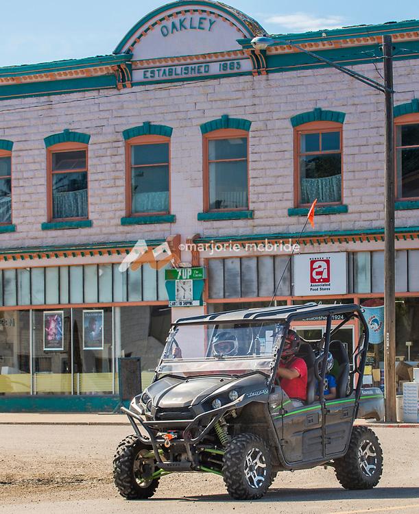 Family in Razor driving a Razor, ATV on Main Street in downtown Oakley, Idaho. MR driving a Razor, ATV on Main Street in downtown Oakley, Idaho. MR
