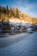 The surface hoar on ice along river shore with sunlit sandstone cliff-face of Ķūķu iezis in cold winter morning, Gauja National park (Gaujas nacionālais parks), Latvia Ⓒ Davis Ulands | davisulands.com