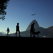 Fitness enthusiasts work out at an outdoor gymnasium overlooking the Early morning walker at Flamengo beach as a plane prepares to land while flying over Suger Loaf Mountain in the distance. Rio de Janeiro,  Brazil. 8th July 2010. Photo Tim Clayton..