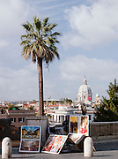 Artists work for sale at the top of The Spanish Steps, looking to Trinita Dei Monti dome in Rome, Italy