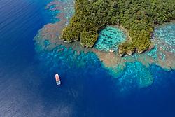Luftaufnahme von Tawali mit Boot, Tawali, Papua Neu Guinea, Solomonensee / Aerial View of Tawali with Boat, Papua New Guinea, Solomon Sea