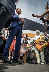 © Licensed to London News Pictures. 16/05/2017. Portsmouth, UK. Liberal Democrat activists look on as party leader Tim Farron (L) gives media interviews outside the Mary Rose Academy special needs school after a visit. The Lib Dems have today announced plans for education and business during campaigning for the general election on June 8, 2017.  Photo credit: Peter Macdiarmid/LNP