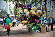 Helium filled balloon seller in Birmingham, United Kingdom. These balloons, all being held in a large bunch depict all sorts of characters from cartoons and tv.