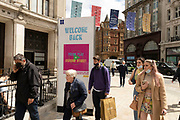People passing a welcome back sign in the shopping district of Oxford Street, some wearing face masks and others not on 26th May 2021 in London, United Kingdom. As the coronavirus lockdown continues its process of easing restrictions, more and more people are coming to the West End as more retail businesses open.