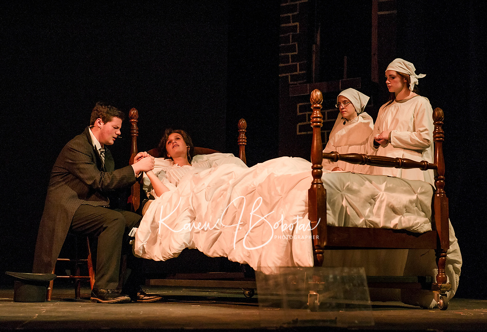 Ryan Witham (Jean Valjean) sits at the bedside of Cyndal VanSteensburg (Fantine) with nuns Lily O'Connor and Katiana Gamache during dress rehearsal for Les Miserables at Gilford High School on Thursday evening.  (Karen Bobotas/for the Laconia Daily Sun)